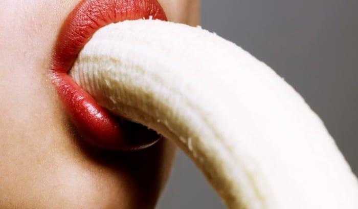 close up of woman eating banana