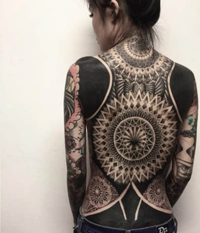 Tribal Back Tattoo with Solid Black SectionsChester of Singapore's Oracle Tattoo shop is the artist responsible for this ornate back tattoo featuring an incredibly detailed tribal design andsolid black sections on the woman's shoulder blades and lower back. This stunning back piece was obviously done by a master tattoo artist and,believe it or not, is still a work in progress.