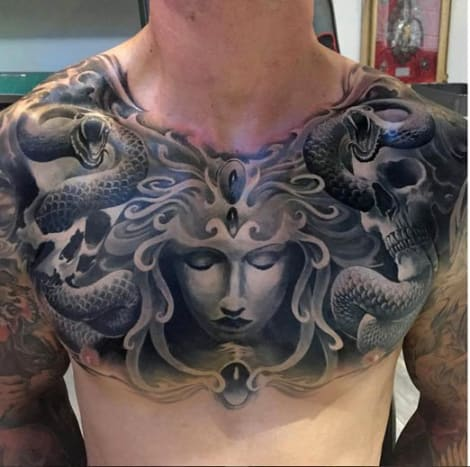 We'd gladly turn to stone staring at this black and grey chest piece by Piotr Dedel
