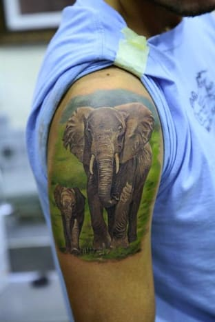 This photo realistic tattoo depicts a cute family of elephants.