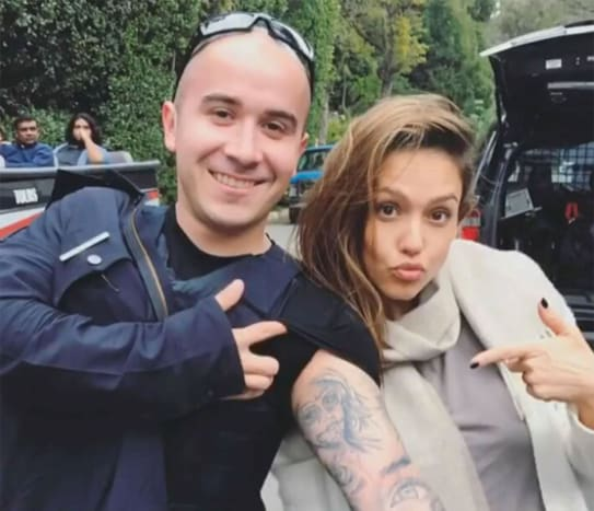 """(Photo: Jessica Alba/Instagram) The man with the tattoo in question is a police officer, and he does indeed have an image of Jessica Alba's face inked in black and grey on his left bicep, done up in the classic Día de Los Muertos-style. Alba posed with the die-hard fan in the street outside of her friend's house, and while she most definitely made the officer's day, the actress all but admitted on Instagram that he made hers as well. It was just earlier this month that Alba met this mega-fan, and when he told her that he had her face tattooed on his arm, she had to see it to believe it. Alba posted a video of her interaction with the officer on her Instagramaccount, captioning the post, """"Definitely one of the more surreal moments of my life – This sweetie pie young officer drove by outside my friend's house and stopped to tell me he had my face tattooed on his arm – of course I HAD to see it! So cool and such a trip."""" The videoso far has more than 540,000 views, and hundreds of comments ranging from """"I guess I need to step up my fan game,"""" to """"That's crazy but @jessicaalba is worth it."""""""