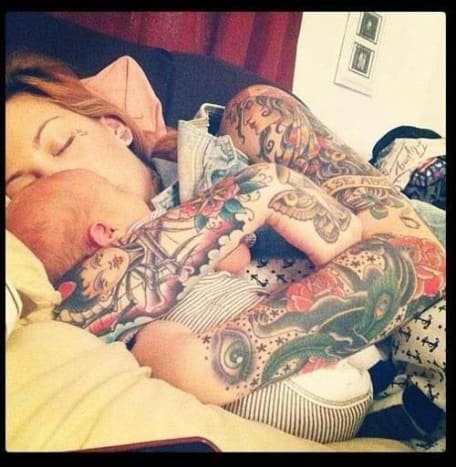 This beautiful tattooed mom is snuggling with her bundle of joy.
