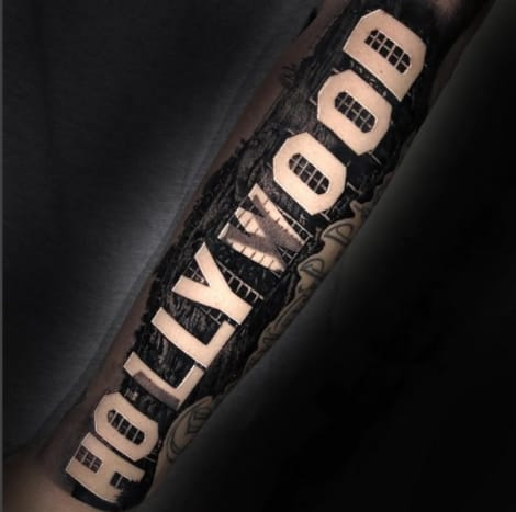 """(Amber Rose's new tattoo, done by Nikko Hurtado.Photo: Amber Rose/Instagram) Although Rose was born in South Philadelphia, she currently lives in Los Angeles, and chose the famous """"Hollywood"""" sign as the subject of her latest tattoo, done by celebrity tattoo artist Nikko Hurtado,owner of the Black Anchor Collectivetattoo shop in Hesperia, California. True to his reputation as a perfectionist, Nikko Hurtado did an incredible job on Rose's arm tattoo, right down to the """"Hollywood"""" letters themselves, the scaffolding holding the letters up, the landscape surrounding the letters, and the chain-link security fence way off in the background. It was on her Instagrampage that Rose shared a photo of her stunning black and grey """"Hollywood"""" tattoo last month, captioning the photo, """"My new tattoo. Great job @nikkohurtado."""" Hurtado posted the same photo to his own account, hinting that there was more work to do on Rose's half-sleeve. """"Thanks for being tough and can't wait to continue it,"""" the tattoo artist captioned the snap, giving a shout-out to Rose. """"More work to come."""""""