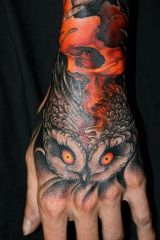 We love the way the skull and the owl go together in this excellent hand tattoo.