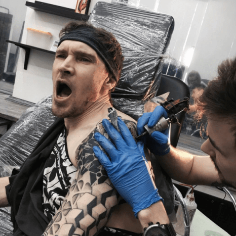 man in pain getting tattooed