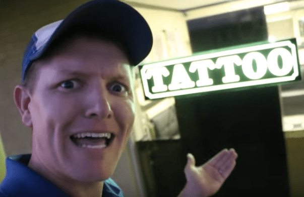 man standing in front of tattoo parlor