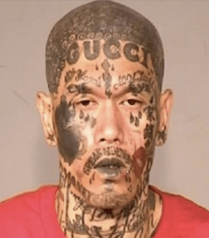 mugshot of man with many head tattoos