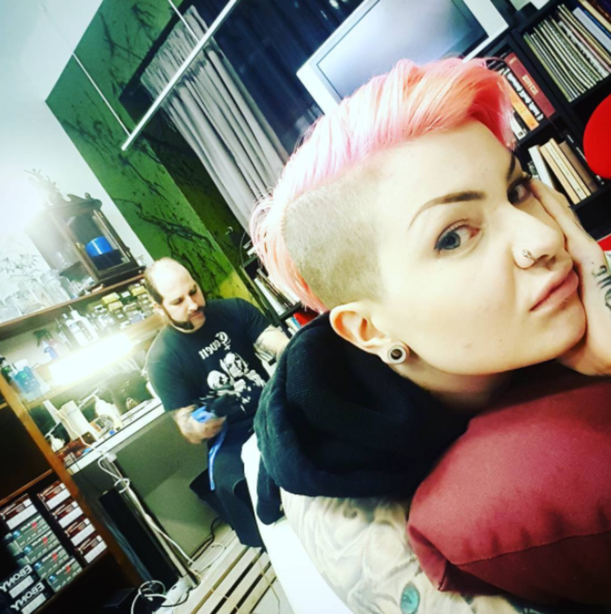 unhappy girl with pink hair getting tattooed