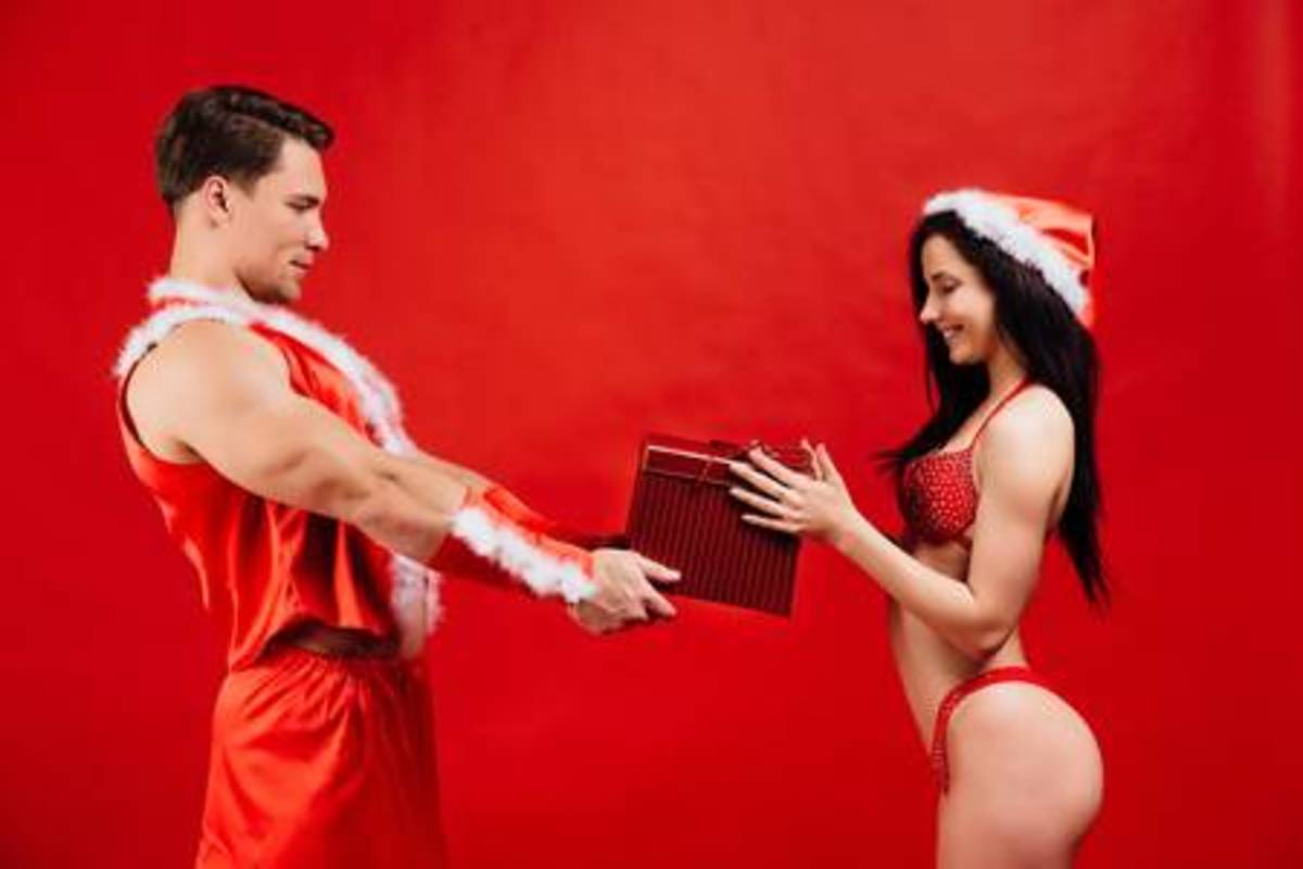 91701582-christmas-and-new-years-gifts-holidays-sexy-santa-claus-gives-a-gift-box-to-hot-girl