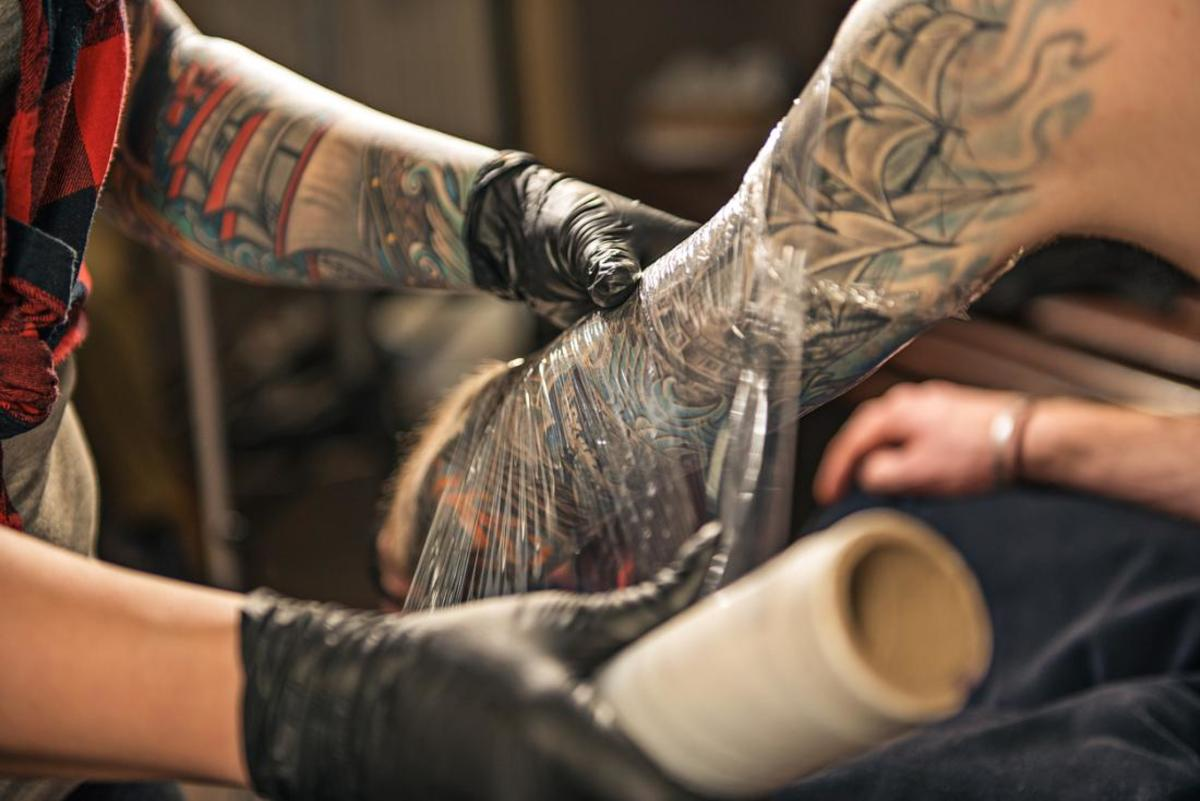 tattoo-artist-wrapping-client-s-arm-in-plastic-clingfilm-to-encourage-tattoo-healing