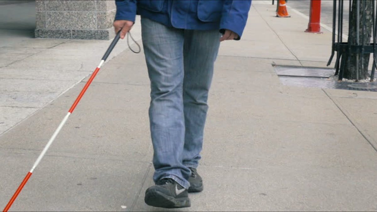 Photo description: Man in jeans and sneakers walking with cane on sidewalk