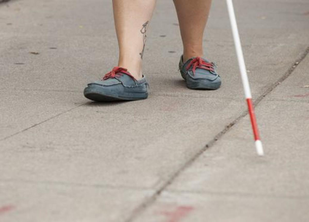 Photo description: Man with boat shoes and exposed ankle tattoo walking with cane on sidewalk