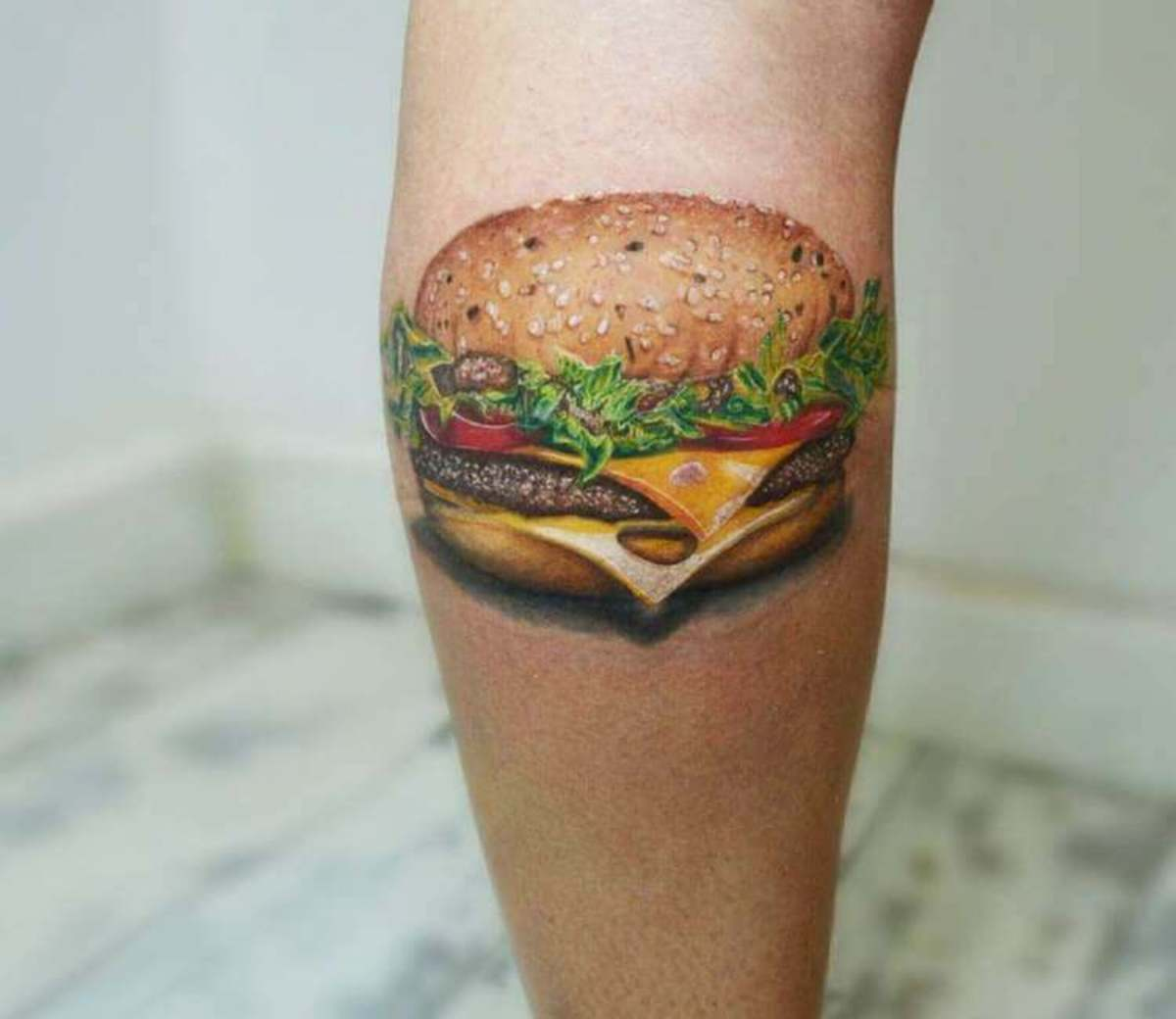 Mmm, who doesn't love Swiss on a burger? Tattoo by Andrea Morales